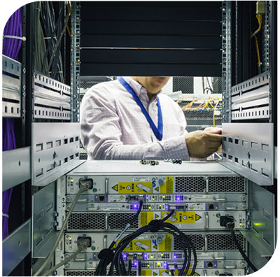 Man using tools to service a sever. View from behind server rack
